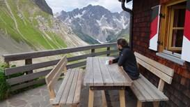 Wanderer sitzt vor Hütte mit Blick ins Tal