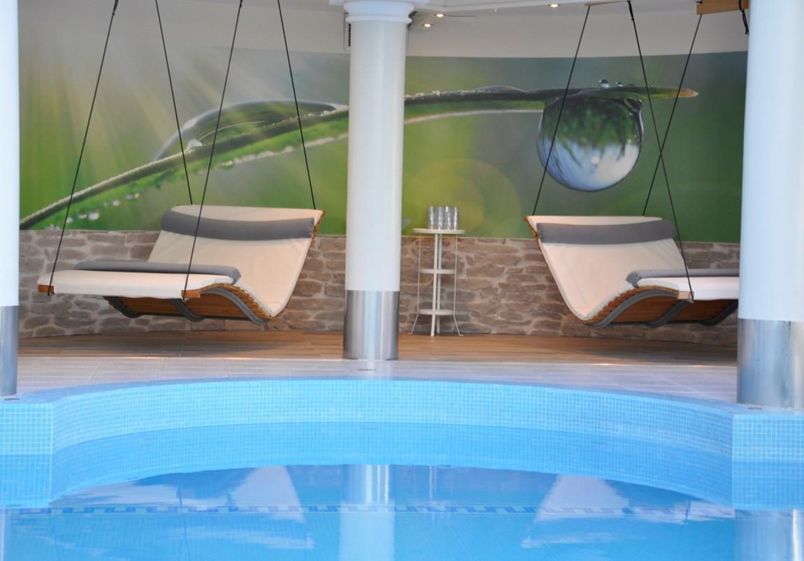 Hängeliegestühle vor Indoor Pool